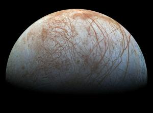 Half the sphere of Europa, an icy white moon with red streaks over its surface