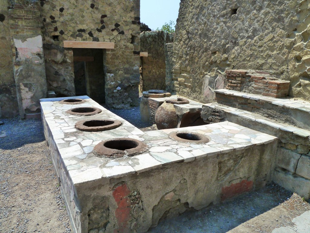 A pale stone block with a big hole in it. This is a thermopolium.